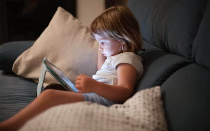 bebé sentado en el sofá y mirando la pantalla