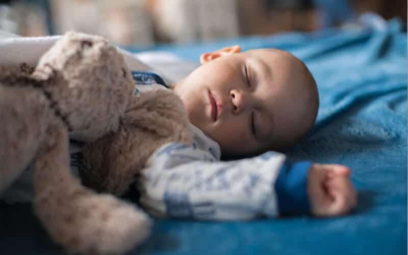 bebé durmiendo en una cama con una manta azul y un osito de peluche.