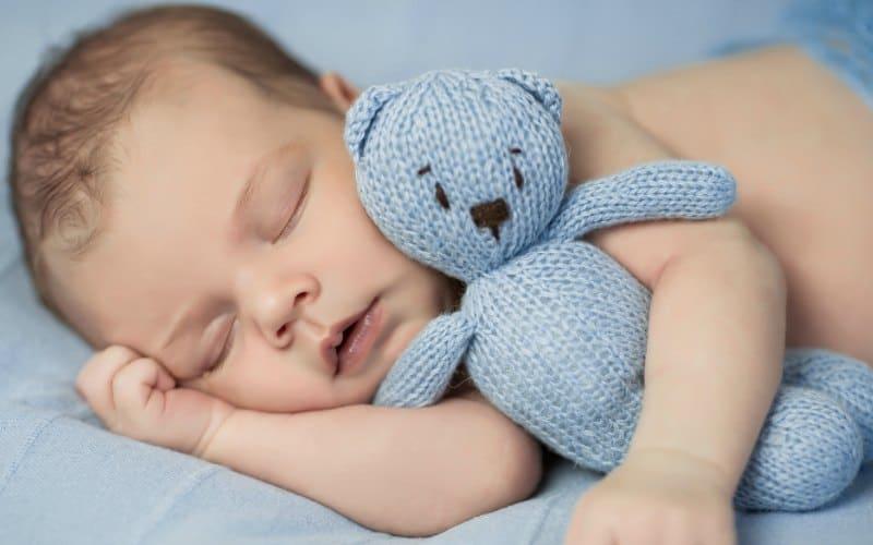 bebé durmiendo con un osito de peluche azul