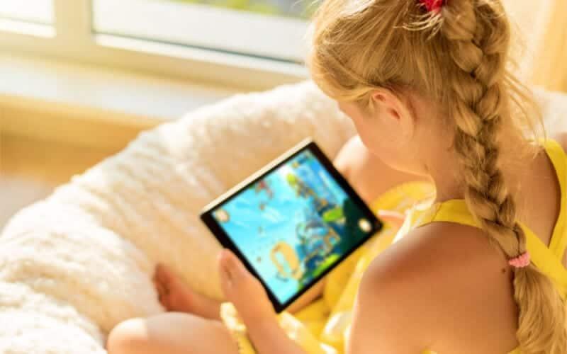 chica de amarillo sentada en la cama y jugando en el iPad