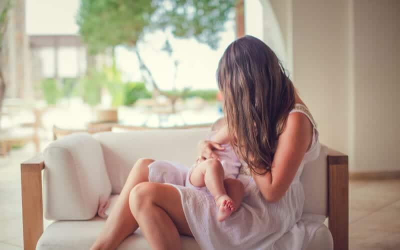 Madre en vestido rosa amamantando a su bebé de 3 meses.