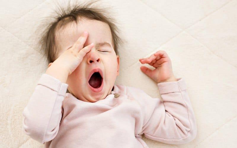 bebé de rosa bostezando y frotándose los ojos