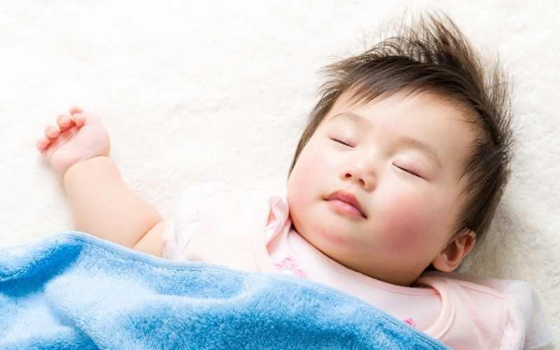 enseña a un niño a dormir en una cama blanca