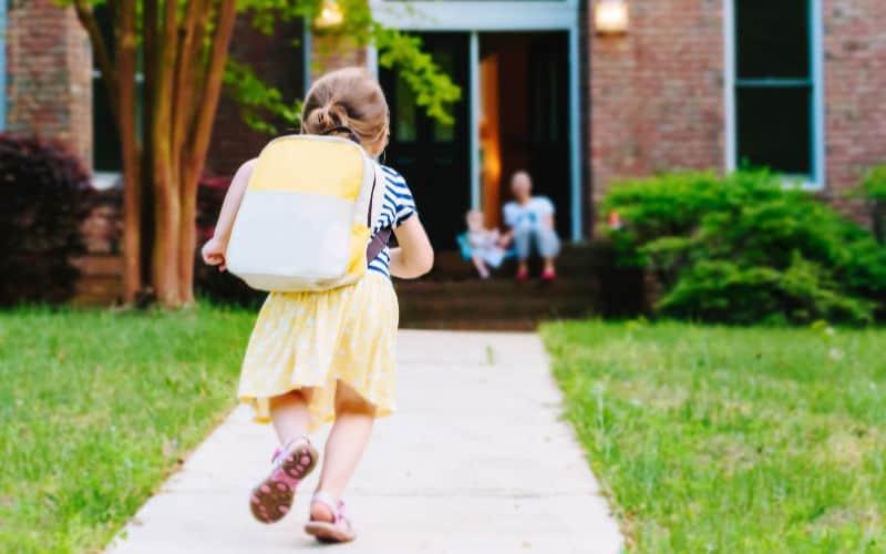 niño corriendo a casa desde la escuela