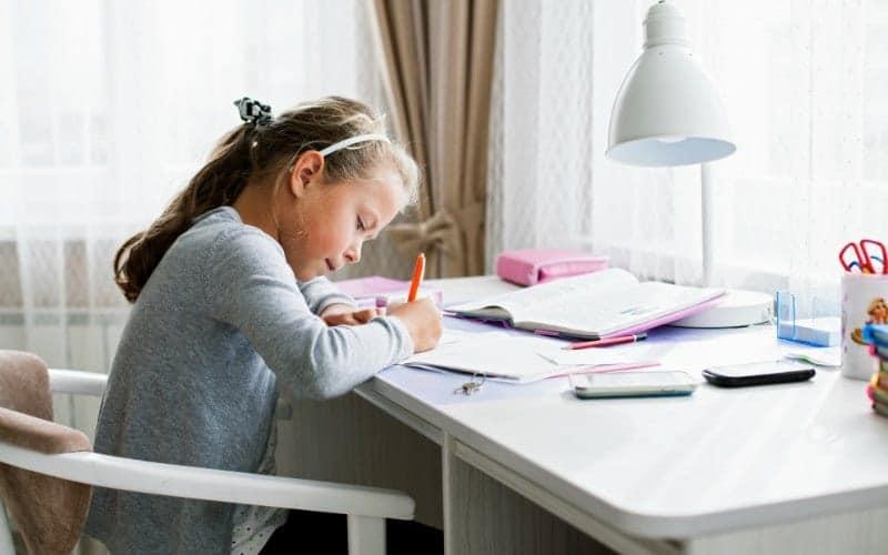 Después de las rutinas escolares, la niña hace la tarea.