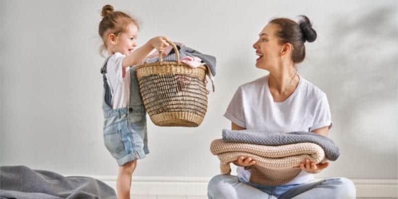 mamá y niño en edad preescolar doblando la ropa