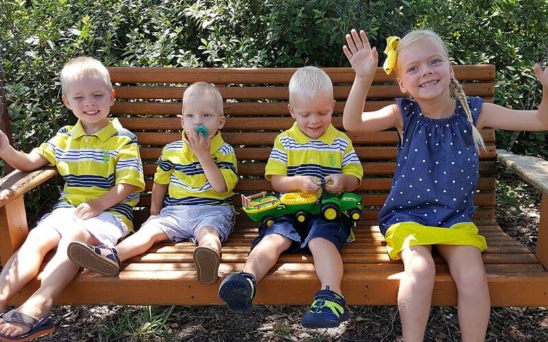 4 niños sentados en un columpio.