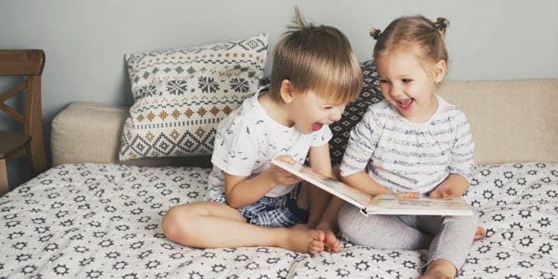 niños pequeños y niños en edad preescolar leyendo libros en la cama