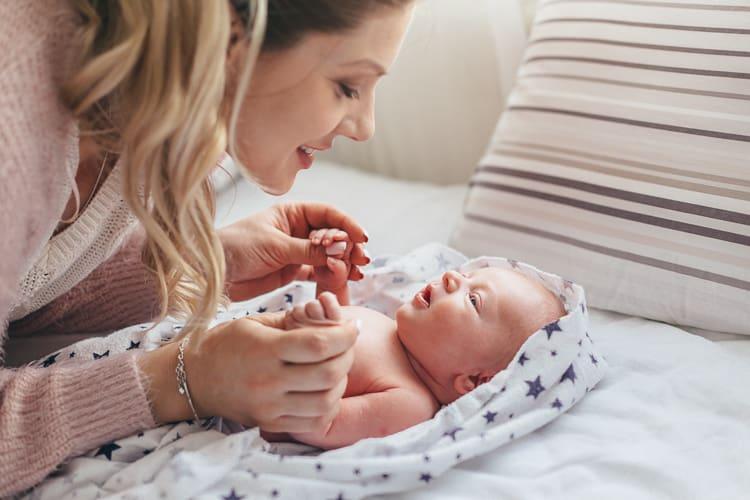 mamá mirando al recién nacido en la cama