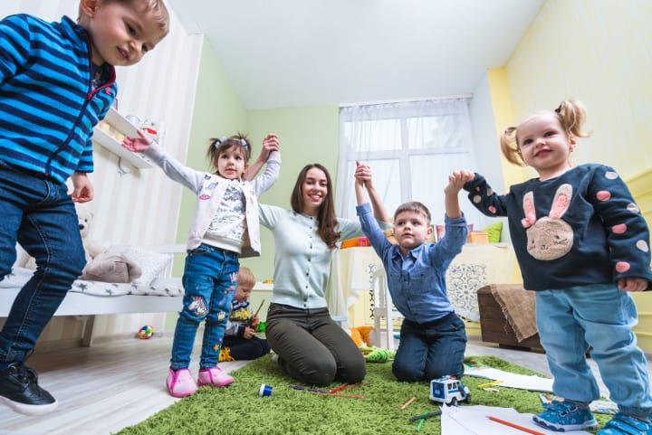 Una feliz profesora coge de la mano a 4 niños de edad preescolar