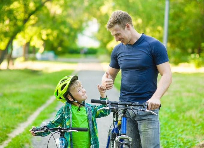 El padre le da al niño un pulgar levantado junto a su bicicleta. Las palabras de aliento a los niños son importantes para aumentar la confianza en sí mismos.
