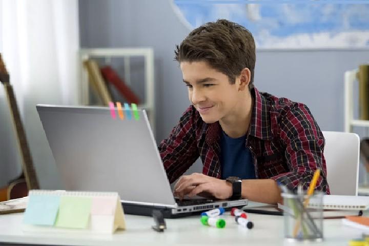 Adolescente que usa el portátil con una sonrisa motivada para estudiar - cómo motivar a mi hijo adolescente para que estudie