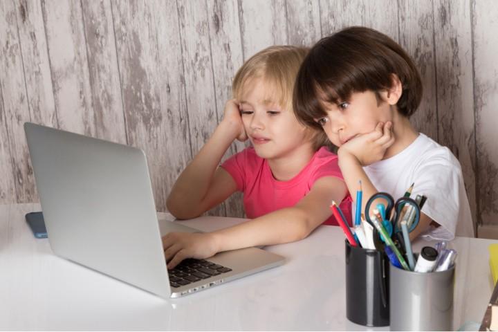 niño y niña miran aburridos al portátil. cómo motivar a los niños en la enseñanza a distancia es la cuestión