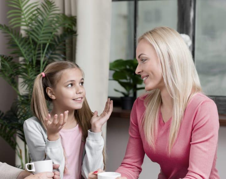 la madre habla con su hija, ésta hace un gesto con la mano que sugiere una disciplina inductiva, un ejemplo de estilo de crianza por inducción