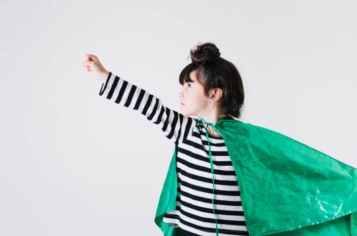 el niño con la gorra verde levanta el brazo y hace una pose de superhéroe, ejemplo de niño con fuerza de voluntad
