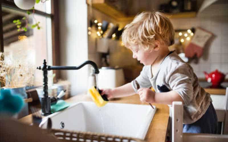 los padres enseñan a los niños a limpiar y preparar platos