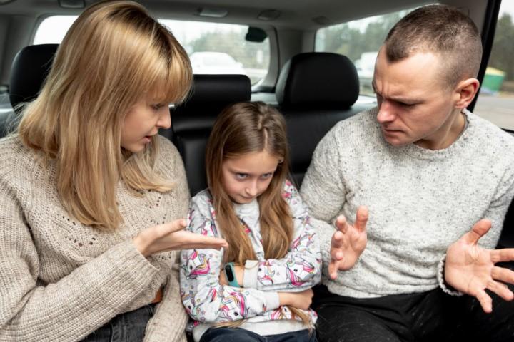 Madre y padre controladores golpean a una niña en el asiento trasero del coche - psicoterapia de padres controladores