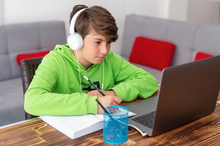niño con auriculares mira la computadora portátil y escribe por qué el aprendizaje a distancia no funciona
