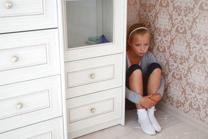 Una niña triste se sienta en la esquina de una habitación junto a una cómoda en un tiempo muerto